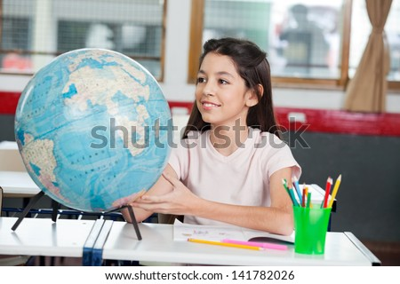 Cute little schoolgirl searching places on globe at desk in classroom - stock photo