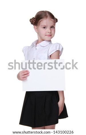 Cute little  schoolgirl wearing white blouse and black skirt and holding paper blank