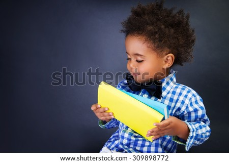 Cute little schoolkid with books in hands over blackboard background, preparing to go to first grade, education in elementary school - stock photo