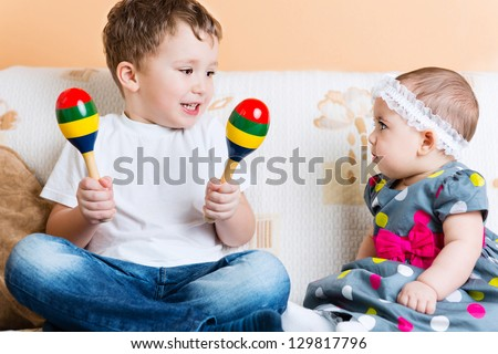 Cute little sister and her brother sitting with maracas on sofa - stock photo