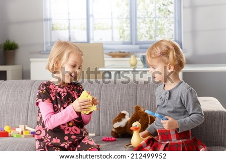 Cute little sisters playing together at home, sitting on sofa. - stock photo