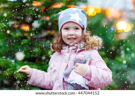 Cute little smiling kid girl with christmas tree. Happy child in winter clothes and toy choosing xmas tree on Christmas market with lights on background. Family, tradition, celebration concept - stock photo
