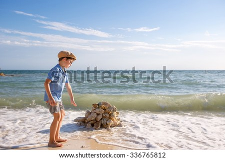 Cute little son building stone castle at beach on Florida summer holiday vacation - stock photo