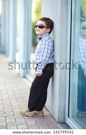 cute little stylish boy in classic style in the city close to the shop window - stock photo