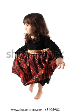 Cute little three year old girl in a fancy plaid and velvet dress dancing on a white background - stock photo
