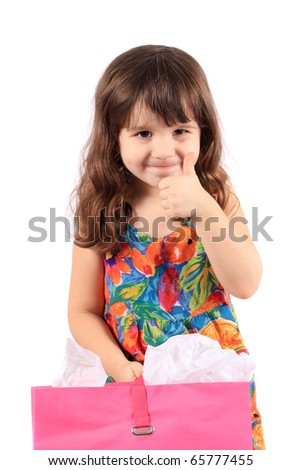 Cute little three year old girl with thumbs up holding a pink shopping back on a white background - stock photo