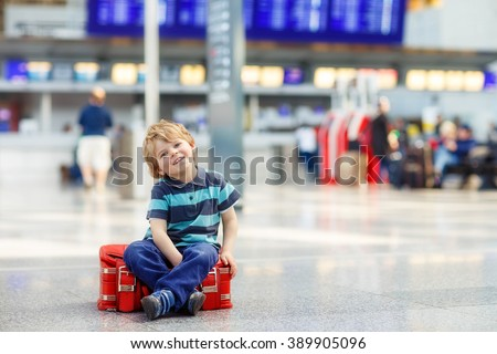 Cute little tired kid boy at the airport, traveling. Annoyd toddler child waiting and sitting on big suitcase. Canceled flight due to pilot strike. - stock photo