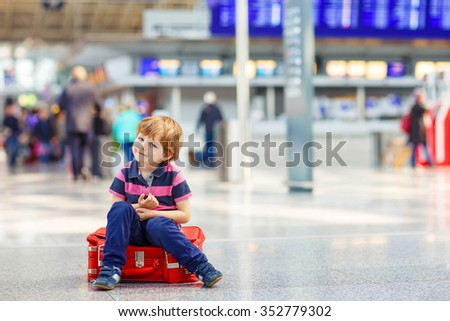 Cute little tired kid boy at the airport, traveling. Upset child waiting and sitting on big suitcase. Canceled flight due to pilot strike. - stock photo