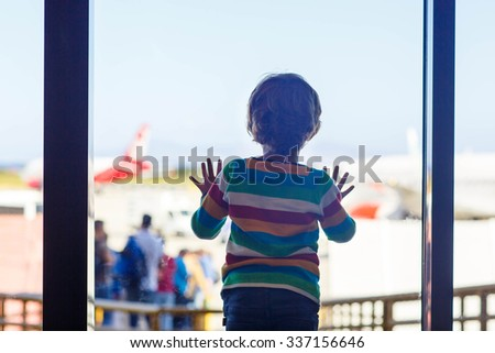 Cute little tired kid boy at the airport, traveling. Upset child waiting near window and looking at plane. Canceled flight due to pilot strike. - stock photo
