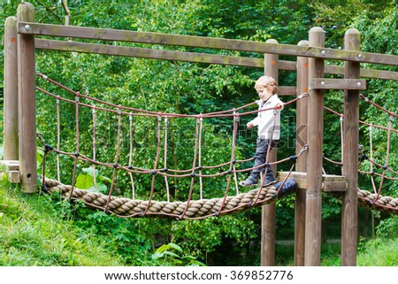 Cute little toddler boy having fun with climbing on playground in summer forest - stock photo