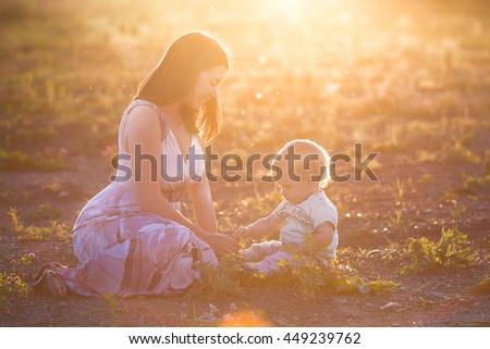 Cute little toddler boy holding his mother's hand. Adorable child walking with his mom in the park on sunny summer day. Happy family with baby on sunset. Childhood, motherhood, family concept - stock photo