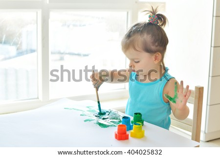 Cute little toddler child painting with paintbrush and colorful paints. Adorable baby girl drawing on white paper near window in light room - stock photo