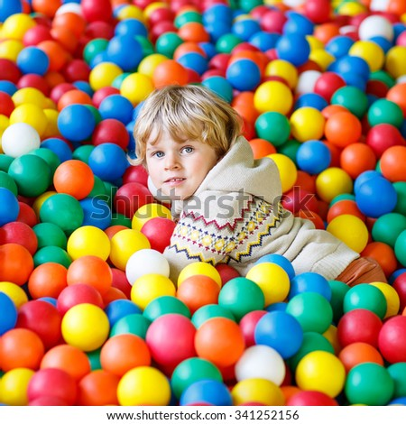 Cute little toddler child playing at colorful plastic balls playground high view. Kid boy having fun indoors. - stock photo
