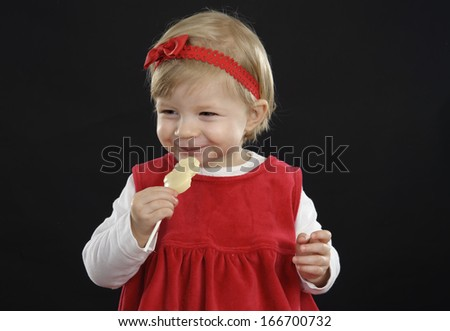 Cute little toddler eating a chocolate lolly on black background - stock photo