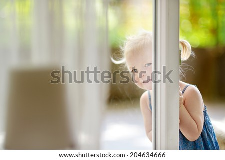Cute little toddler girl peeking into a window on beautiful warm and sunny summer day - stock photo