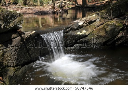 Cute little waterfall at Bailey's Ravine in Franklin, CT.  This is one of a series of cascades that goes on and on through the forest. - stock photo