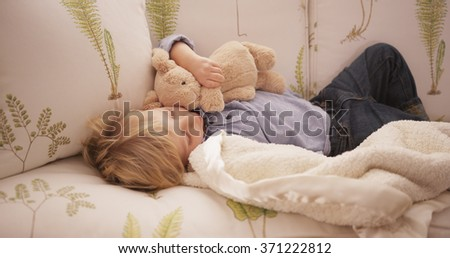 Cute little white boy lying on a sofa. - stock photo