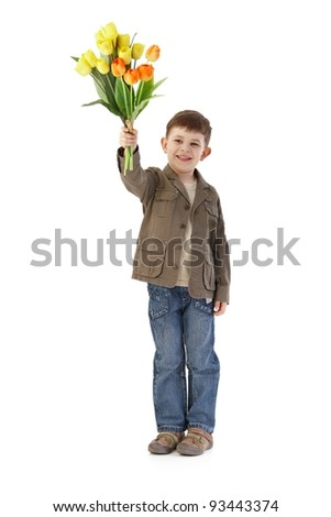 Cute little 5 year old kid holding a bouquet of tulips, smiling.? - stock photo
