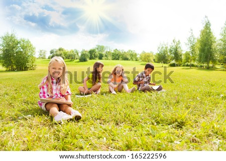 Cute little 6 years girl drawing in park outside sitting on the grass on sunny day