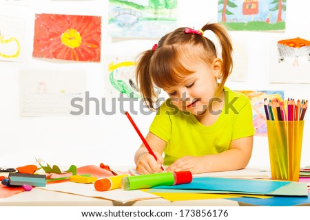 Cute little 3 years old girl in yellow shirt and pony tails draw with pencil in the art class - stock photo