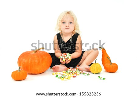Cute littlest witch holding candy and pumpkins around. - stock photo