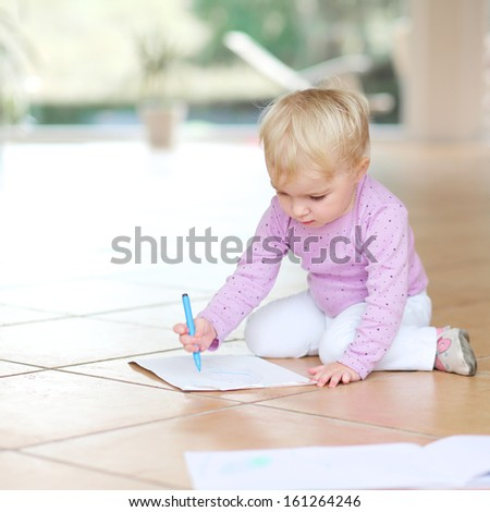 Cute lovely baby girl plays indoors drawing with colorful pencils sitting on tiles floor - stock photo