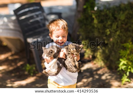 Cute lovely boy with kitten in a park - stock photo