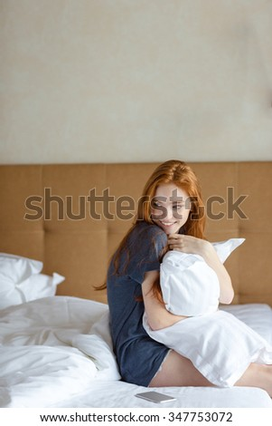 Cute lovely playful young lady hugging pillow and sitting on bed in her apartment - stock photo