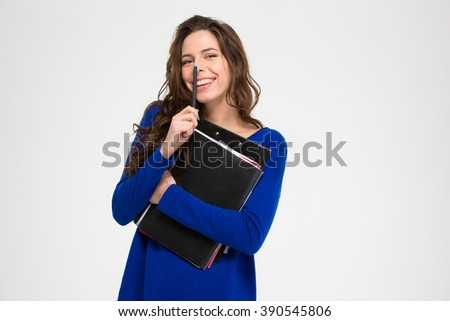Cute lovely smiling young woman standing with folders and pen over white background - stock photo