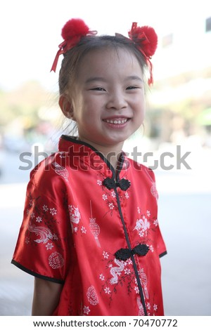 Cute lovely sweet little asian girl on Chinese dress with smiling face in home background - stock photo