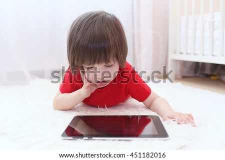 Cute lovely 2 years boy in red t-shirt with tablet computer at home