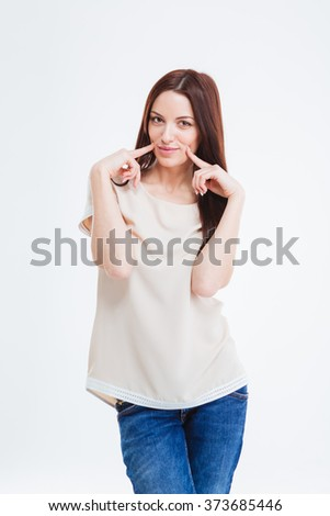 Cute lovely youn woman in blouse and jeans standing and touching her cheeks over white background - stock photo
