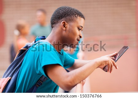 cute male african college student using tablet computer  - stock photo