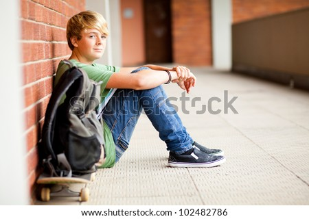 cute male high school student sitting on floor - stock photo