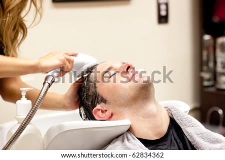 Cute man having a shampoo in a hairdressing salon - stock photo