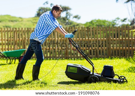 cute man mowing lawn in the backyard of his house - stock photo