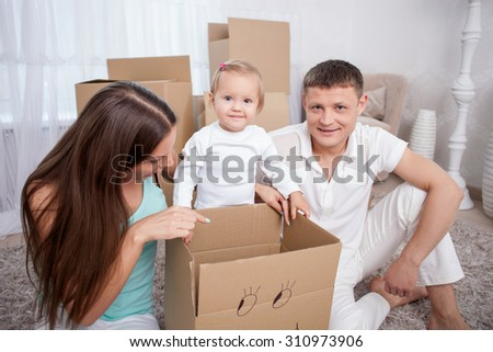 Cute married couple and their child are packing their staff for move. They are sitting near the box. A woman is pointing her finger at it with interest. The father and daughter are smiling - stock photo