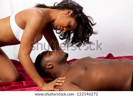 Cute married couple in sexual foreplay together, he is reclining and she is kneeling over his head, in romantic  feeling of love and acceptance - stock photo