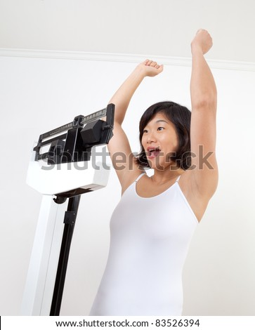 Cute mature woman on a weight scale cheering happily at reaching her target weight. White background