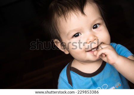 Cute mixed race Asian Caucasian baby boy happily playing with a black background - stock photo