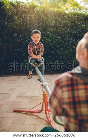 Cute mixed race Asian Caucasian brothers play on a seesaw in the backyard of their suburban home. Filtered effects - stock photo