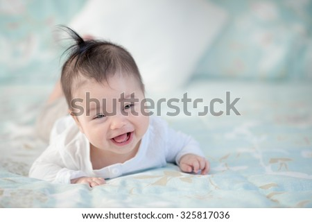 Cute mixed race Asian Caucasian 6 month old baby boy plays inside on a bed - stock photo