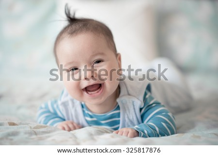 Cute mixed race Asian Caucasian 5 month old baby boy plays inside on a bed - stock photo