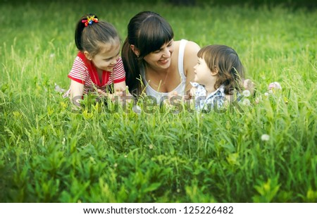 Cute mom and daughters relaxing on the lawn - stock photo