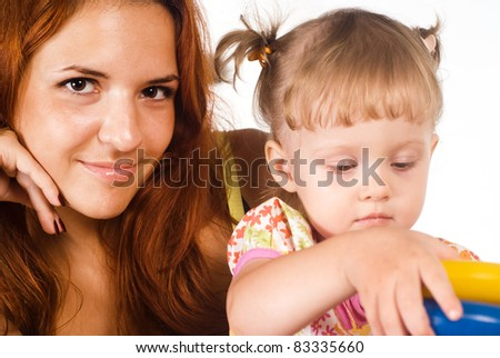 cute mom and her daughter sitting on a white