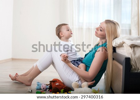 Cute mom is sitting on flooring and holding her little son. They are looking at each other with love. The boy is holding female hand - stock photo