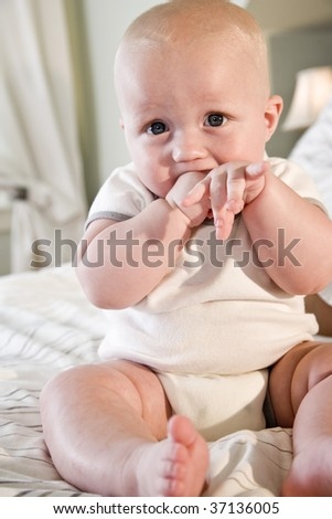 Cute 7 month old baby sitting on bed with hand in mouth - stock photo
