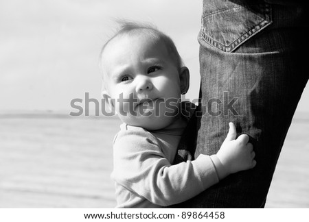 cute 10-month old baby with father's leg - stock photo