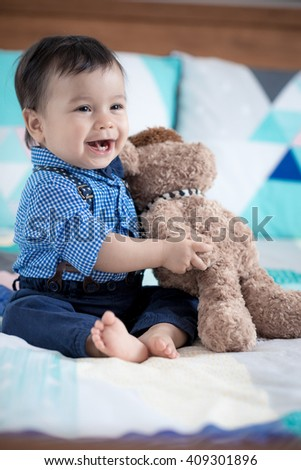 Cute 11 month old mixed race Asian Caucasian boy dressed in braces and bow tie plays cheerfully with his brown teddy bear on a colourful geometrically shaped bed cover - stock photo