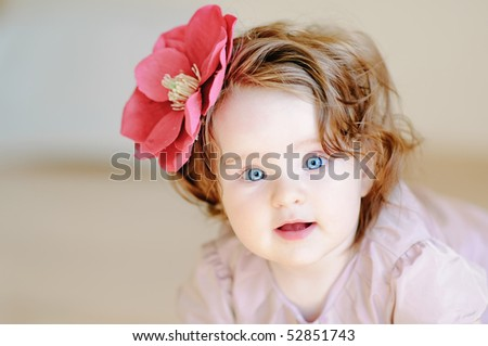 Cute 9-months baby-girl with flower on her hair smiling - stock photo